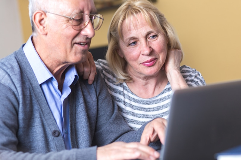 Happy senior couple using laptop at home.